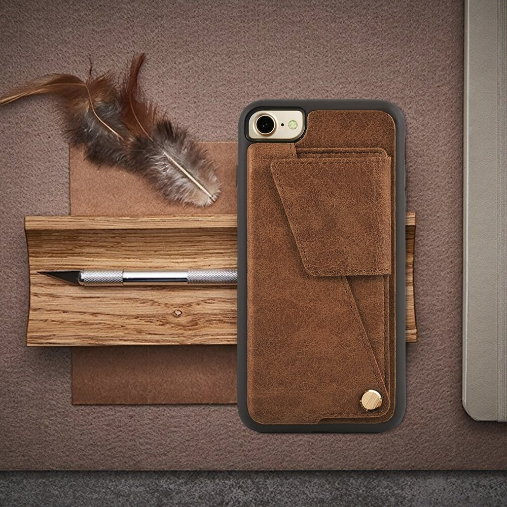 the brown leather card holder photographed on a work desk next to a pen and a feather