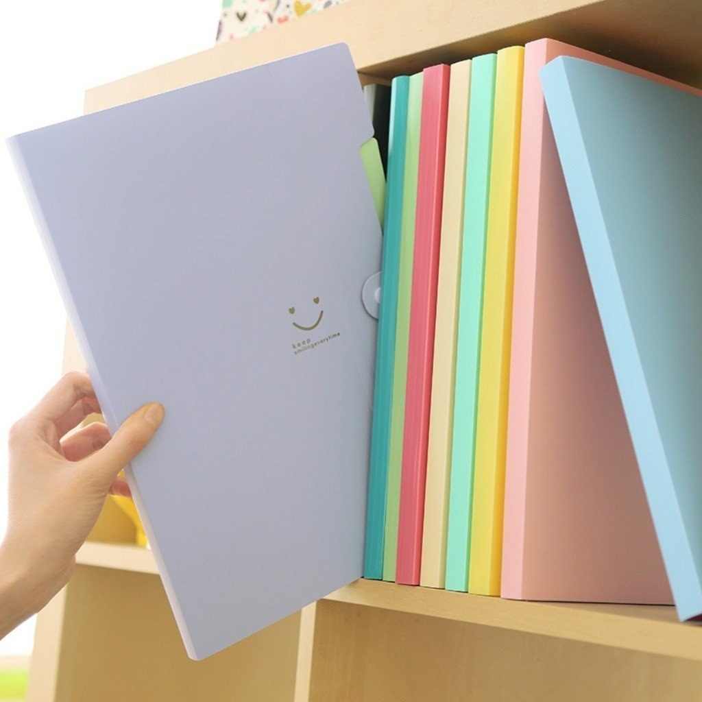 The accordion file folder in purple being pulled out of a shelf with an assortment of other in different colors in it