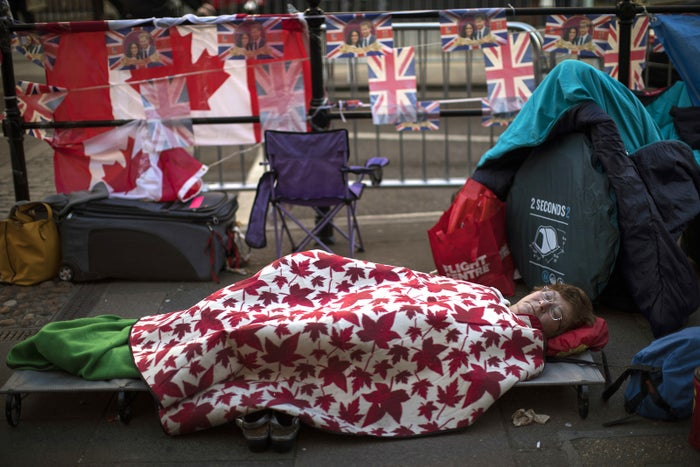 A woman sleeps outside Windsor Castle ahead of Prince Harry and Meghan Markle's wedding in Windsor, England.
