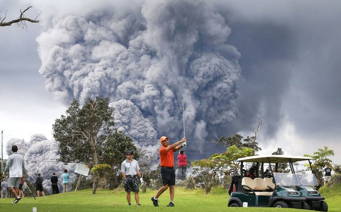 People play golf as an ash plume rises in the distance from the Kilauea volcano on Hawaii's Big Island on May 15, in Hawaii Volcanoes National Park.