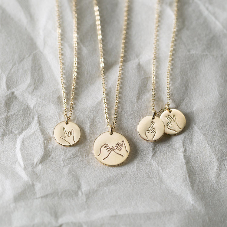 Four gold charm necklaces, each with a different hand gesture on the small disc detail