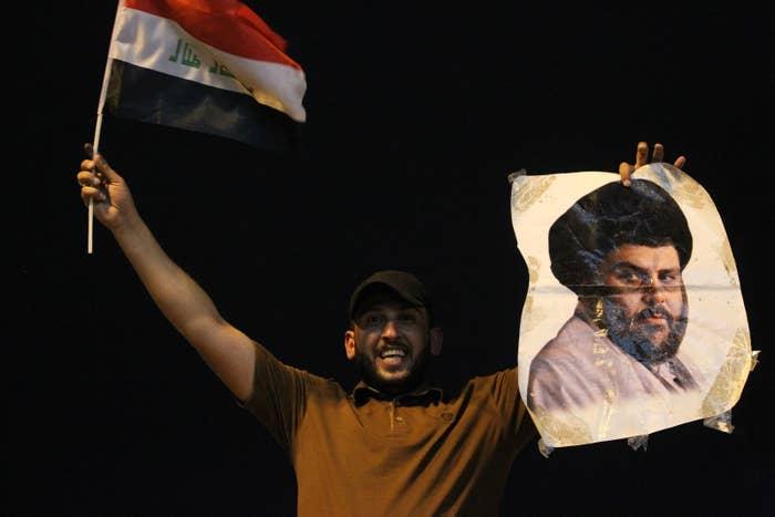 An Iraqi man celebrates with a picture of Shiite cleric Muqtada Sadr.