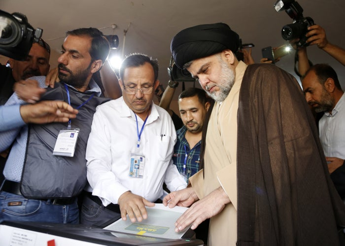 Al-Sadr puts his ballot through an electronic counting machine into a ballot box at poll station in the central holy city of Najaf on May 12, 2018