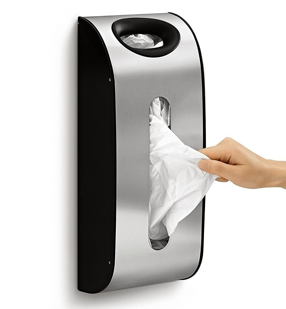 a hand removing a bag from the bag dispenser