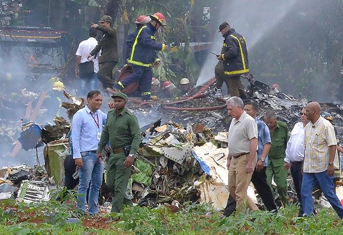 Cuban President Miguel Díaz-Canel, in khaki pants, visits the site of the crash.