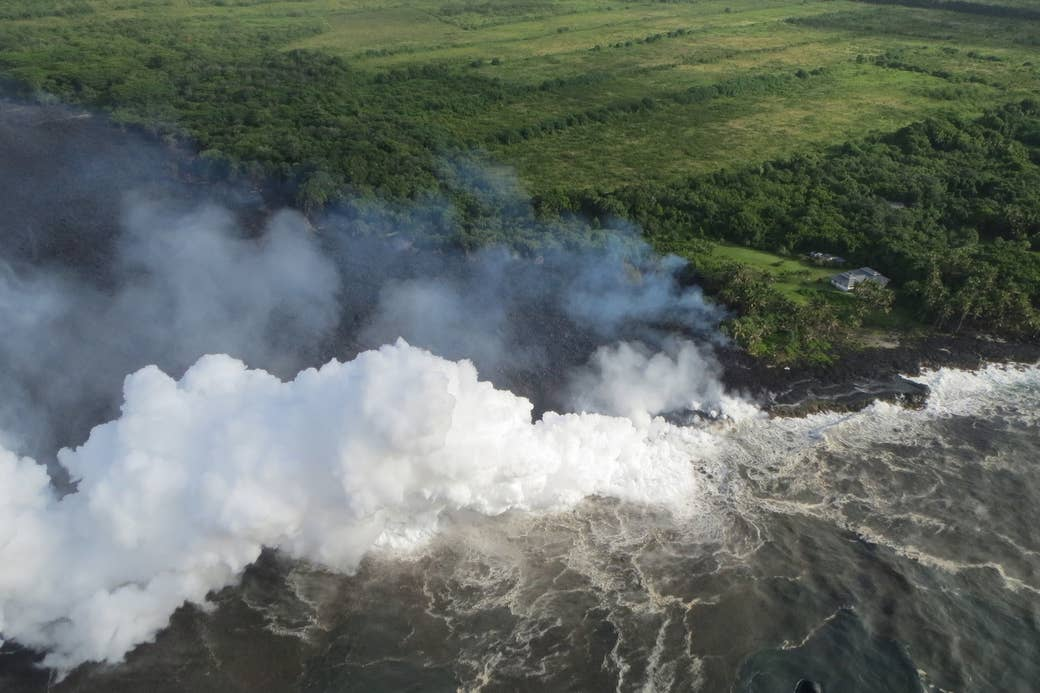 A photo taken Sunday morning from a helicopter shows where lava entered the ocean. A home is seen at the edge of the flow.
