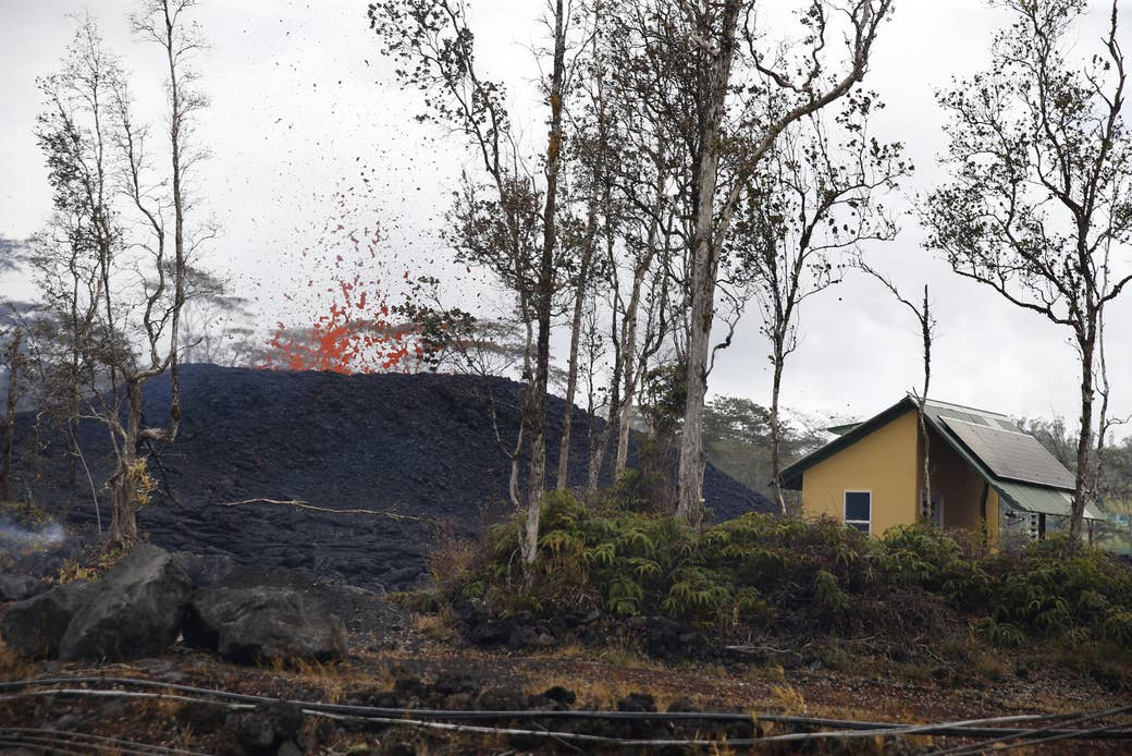 A structure is seen next to an erupting lava fissure on Pohoiki Road on Friday. Three shelters have been opened for people who have had to evacuate because of the lava threat.