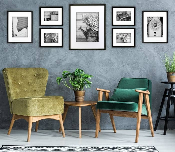 A set of seven differently sized photo frames arranged on a wall