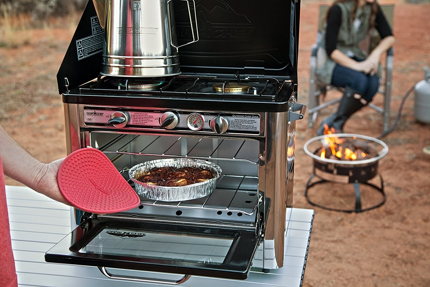 The oven on a camp table; there's coffee on the stove and the oven's open to show a tray of cinnamon rolls