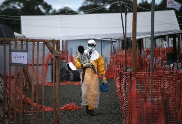 An MSF health worker carries a child suspected of having Ebola in Liberia during the 2014 outbreak.