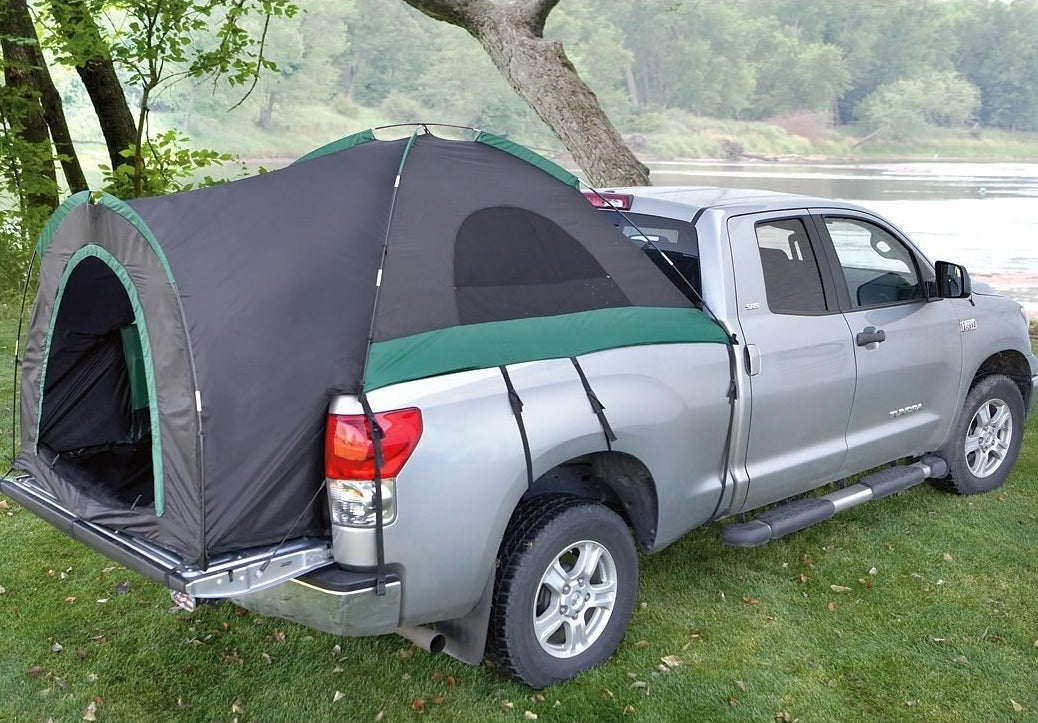 The tent set up in a truck bed, with straps secured down in the wheel well and under the car, and the entrance at the tailgate