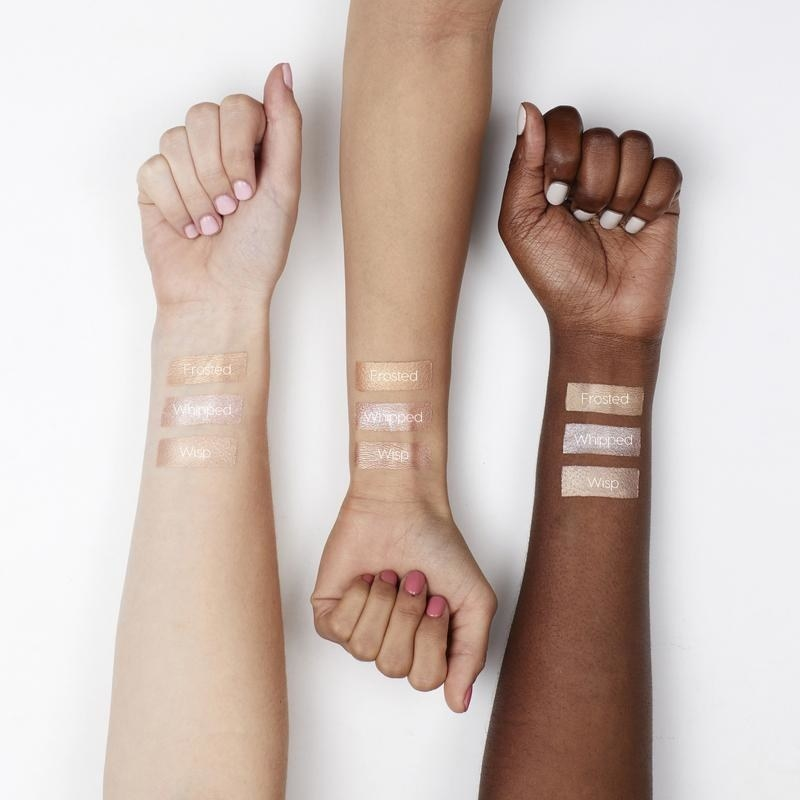 """Three arms in three different skin tones showing swatches of three Colourpop highlighter shades, one of which is """"Wisp"""""""