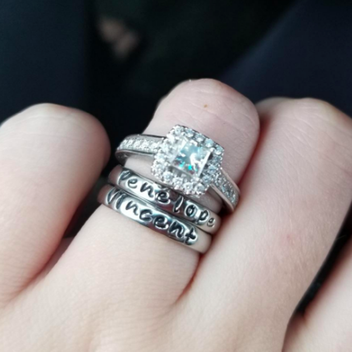 same set of silver stackable rings below wedding band on reviewer's ring finger