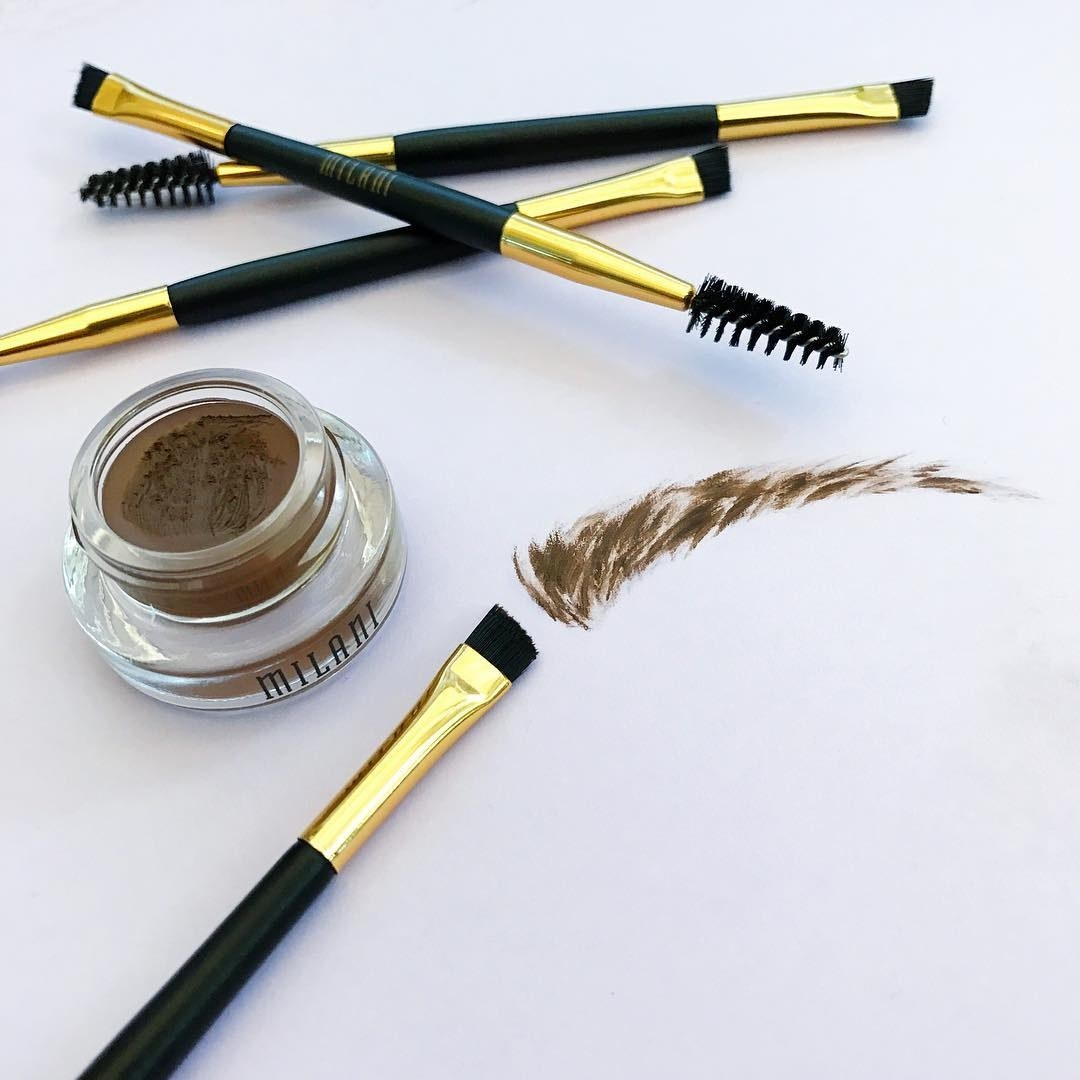 The Milani brow color, which comes in a gel pot, plus the double-sided applicator (one side angled brush, one side spoolie), plus a fake eyebrow drawn on a surface to show what the strokes of the gel color look like