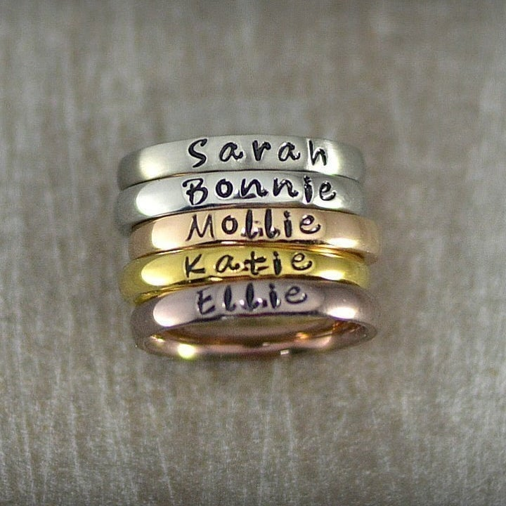silver, rose gold, and gold stackable rings that say Sarah and other names on front