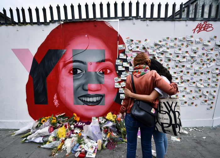Two women look at flowers and written notes left on the Savita Halappanavar mural, as the Irish referendum on the country's abortion laws takes place on May 26, 2018 in Dublin, Ireland.
