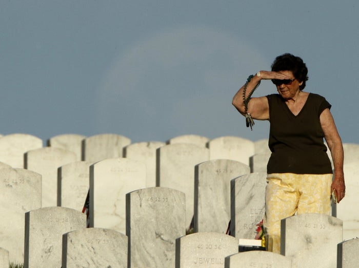 Carol Page, from Leavenworth, Kan., looks for her parent's graves at Leavenworth National Cemetery on Sunday.