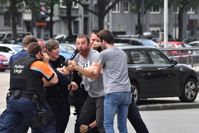 """Police officers in Liège restrain a distressed man near where an armed man shot and killed police officers before being """"neutralized."""""""