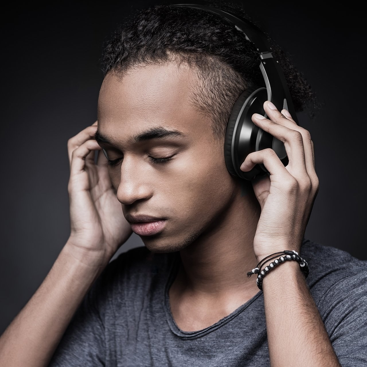 A model putting the headphones on over their ears