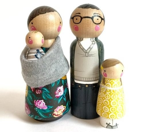 product shot of two peg parents, one holding a baby, and a peg child