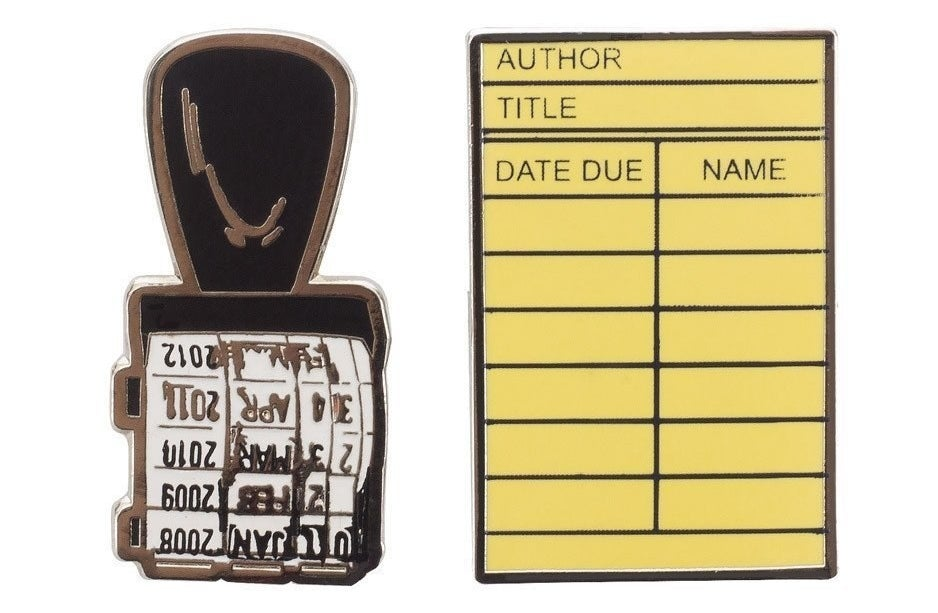 enamel pins made to look like a library stamp and library checkout card