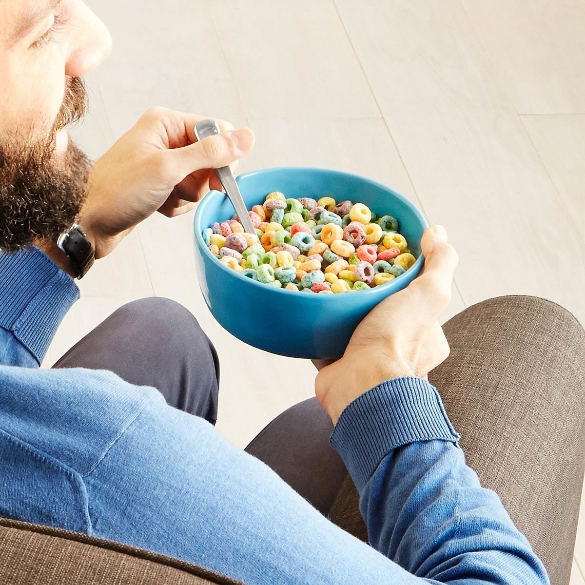 man easily holding a bowl on the couch