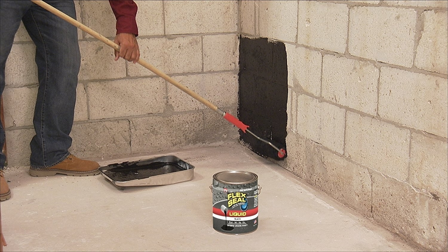 person in a basement rolling the product on a wall