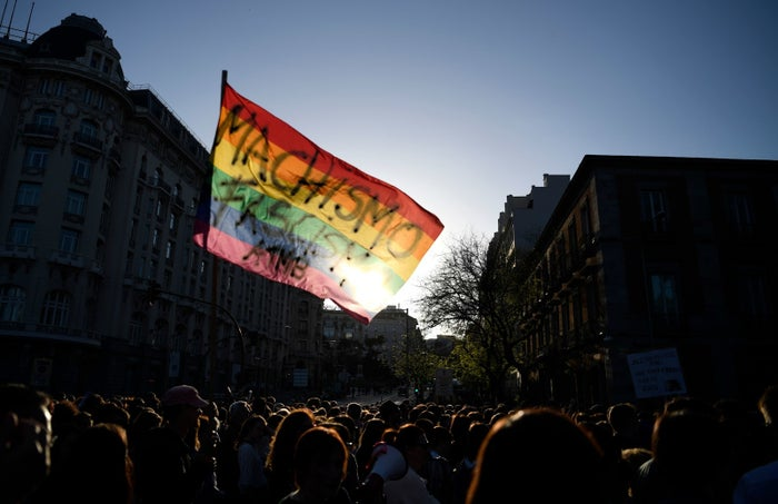 """Demonstrators wave a pride flag with a text reading """"Machismo, fascism"""" during a protest in Madrid on May 4, 2018."""