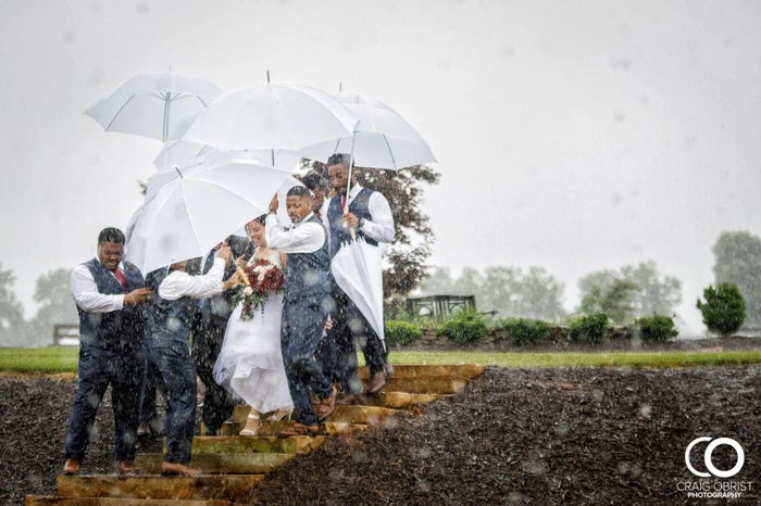 """They had waited a half an hour past their ceremony start time of 5 p.m. to let the rain pass, and when it didn't, """"a couple of the groomsmen suggested they walk the bridesmaids down and then come back and get me to cover me and so that they could hold my dress so it wouldn't get wet because by that time it was pouring,"""" Diana said."""