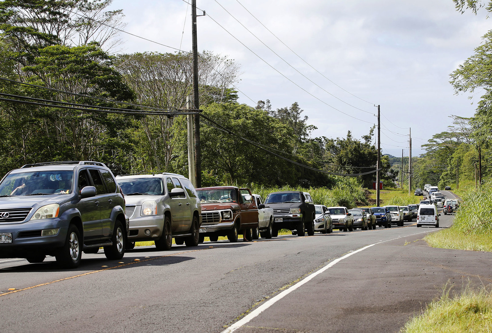 Residents of the Leilani Estates wait in a line to enter the subdivision to gather possessions from their homes.
