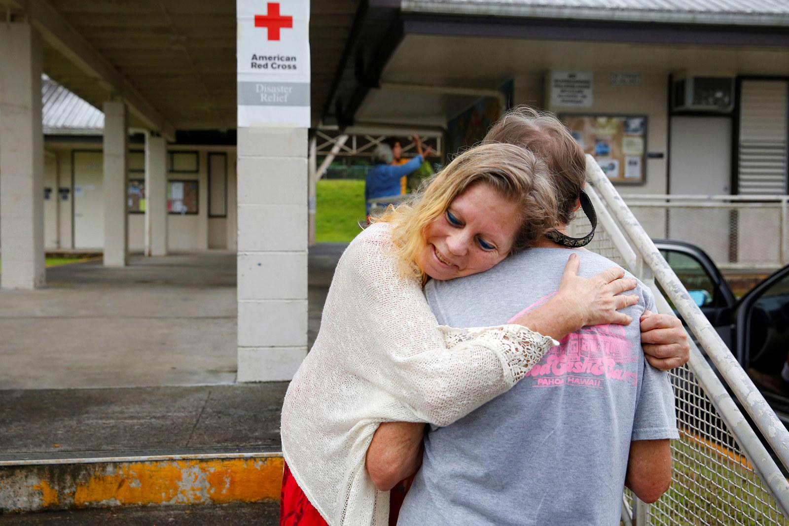 Carolyn McNamara, 70, hugs her neighbor Paul Campbell, 68, at an evacuation center in Pahoa.