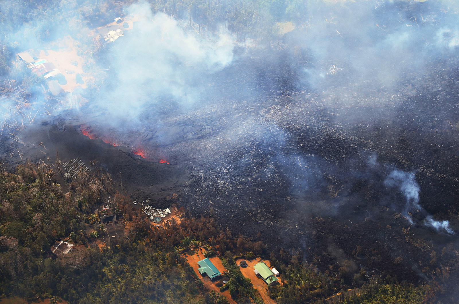 Lava from volcanic fissures slowly advance and overtake structures and trees in Leilani Estates.
