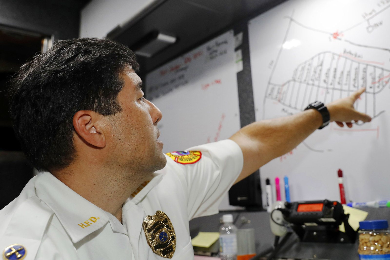 Hawaii Fire Department Battalion Chief Darwin Okinaka points to a map where recent volcanic eruptions have occurred.