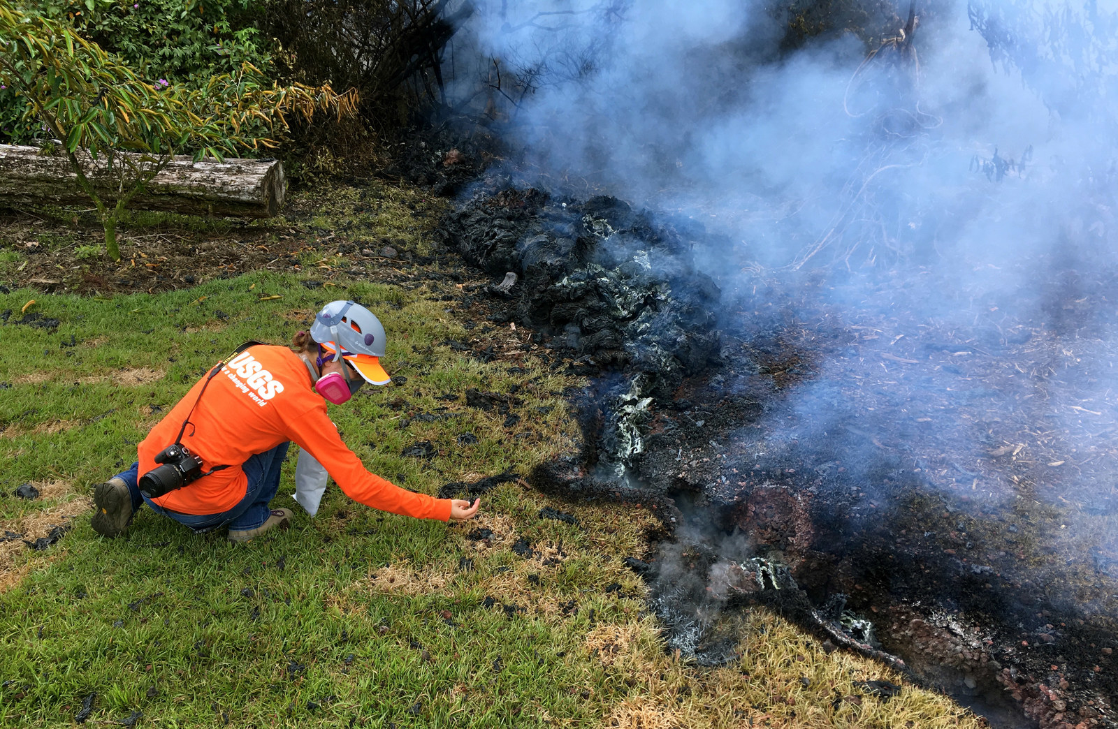A geologist collects samples of spatter for laboratory analysis on May 6 in Leilani Estates.