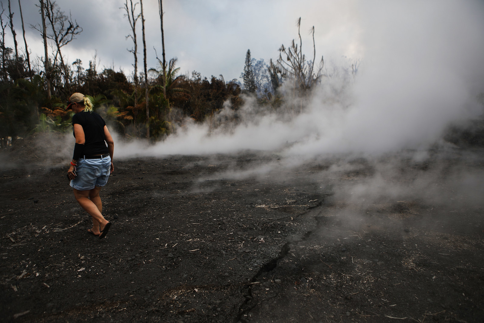 A resident inspects fissures located near her home, which remains standing, in the Leilani Estates in the aftermath of eruptions on May 7.