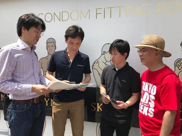 東京レインボープライドの会場でコンドームメーカーの不二ラテックスに職場健診へのHIVと梅毒の検査導入を持ちかける横幕能行さん(左端)と共同研究者の生島嗣さん(右端)