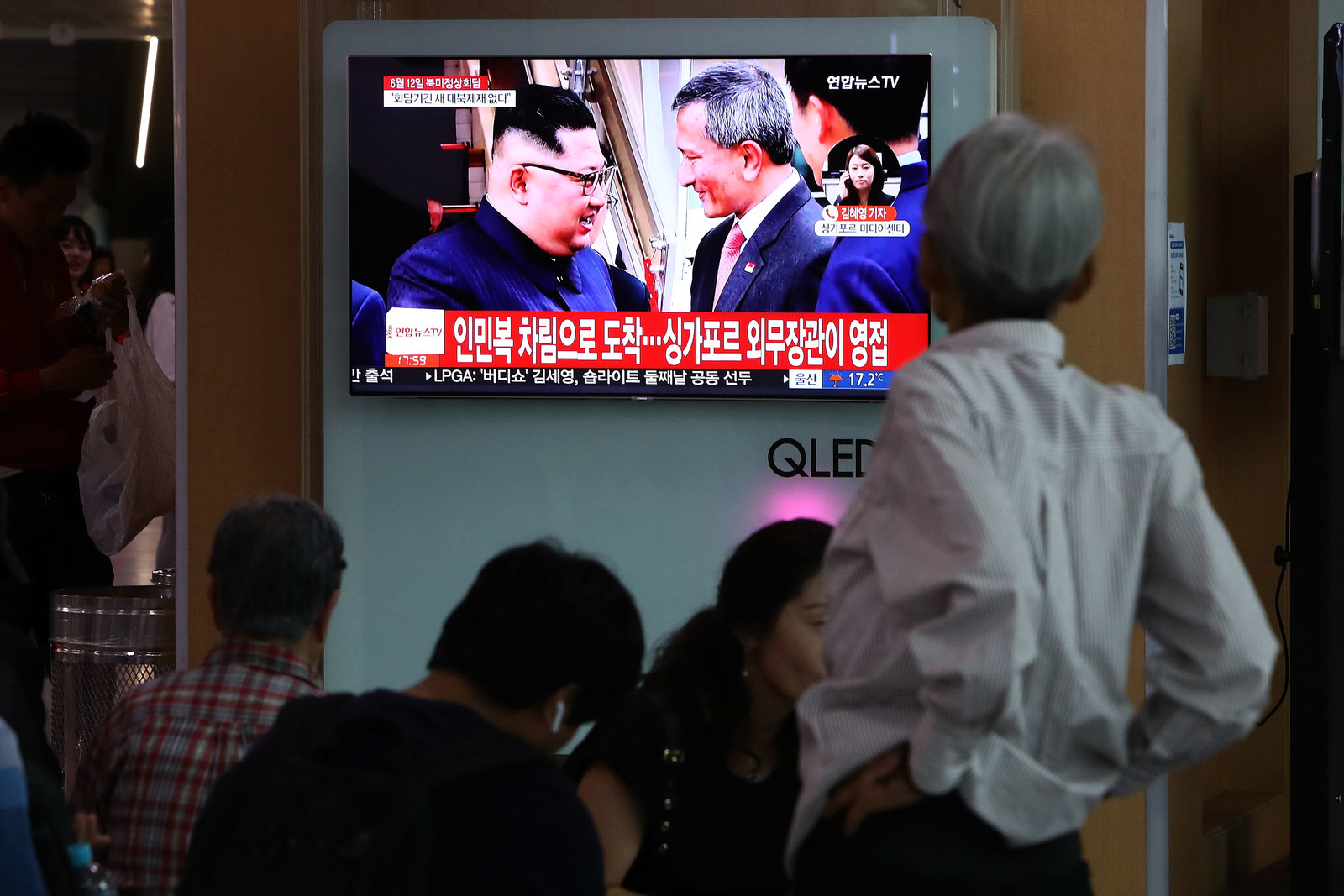 South Koreans watch news coverage on a screen at the Seoul Railway Station as North Korean leader Kim Jong Un arrives in Singapore.