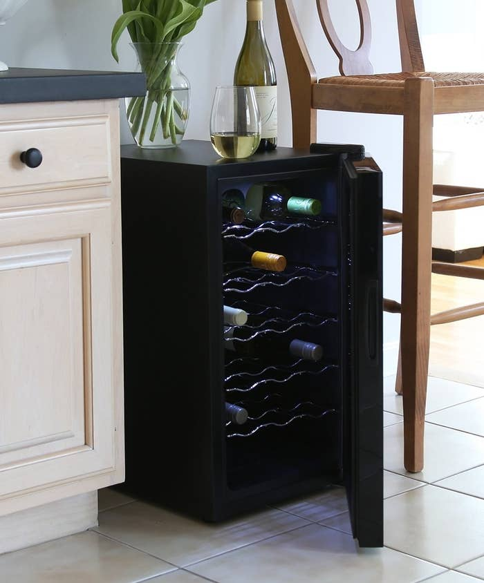 """This freestanding wine cooler created the ideal temperature for wines that should be stored in 54º–64ºF. It has 100% customer satisfaction guarantee. Promising review: """"I bought this for my wife in our new house. We had custom cabinets and a huge island with a large void of unused space in the one side where the seating overhand was. I have since placed this chiller in that space and it works perfectly and is out of the way of everything. It has its own little hideaway undisturbed and has worked flawlessly since day one. My wife generally drinks sweeter wines and the temps available for this are perfect for storage and consumption of her choice drinks. The blue light inside adds a really nice affect when opening the cabinet and all controls are easy to use. It operates very quietly and I truly cannot even remember ever hearing it running. The smoked color glass provides a great look and the sleekness of it all really makes it a nice piece for display if need be. I have had no issues with heating inside the cabinets as I have plenty of space in the back of the machine. I will buy again and recommend highly to those looking into these products."""" —RayGet it from Amazon for $159.99+ (available in two colors)."""