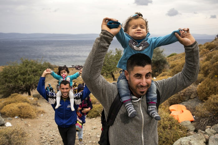 A line of refugees and migrants head up from the beach after landing on the Greek island of Lesbos from Turkey on Oct. 11, 2015.