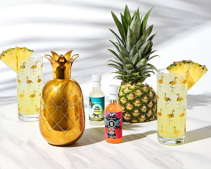 """It comes with a golden pineapple cocktail shaker, two flamingo print highball glasses, and two cocktail mixes (for a Mai Tai and a piña colada) — all your need to add is alcohol and ice!Get it from Amazon for $29.99.Promising review: """"Nothing says vacation more than pineapples and flamingos! First of all, I really love how this is presented...in a beautiful box and packaged flawlessly. It comes with a unique story which is a great touch. I was pleasantly surprised by the weight of the cocktail shaker. This set looks great on our bar!"""" —Kindle Customer"""