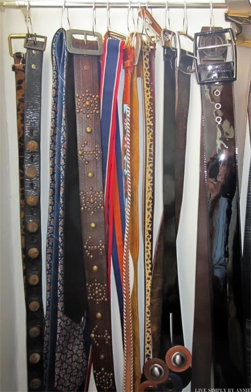 Row of belts hung on a small rod with the curtain rings