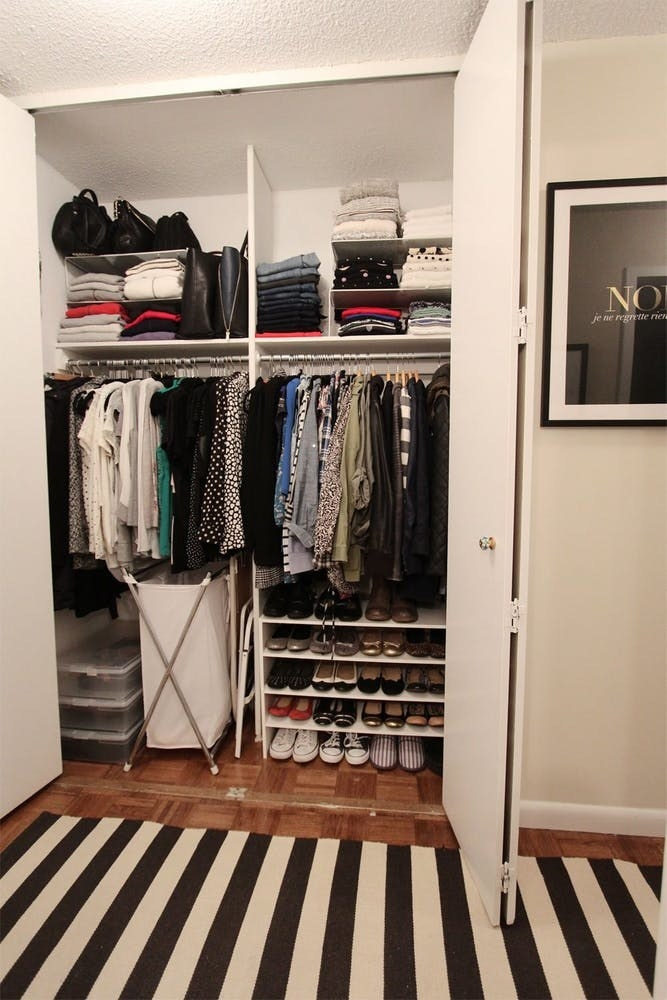 A closet with lots of vertical space above the top closet shelves, so smaller shelves are stacked on top and store various items