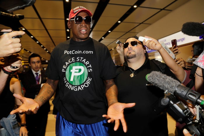 Former NBA basketball player Dennis Rodman, and Chris Volo, right, arrive at Singapore's Changi Airport on June 12.