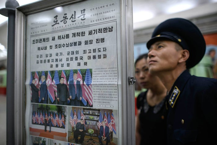 A train conductor reads the latest edition of the Rodong Sinmun newspaper showing images of North Korean leader Kim Jong Un meeting with president Donald Trump during their summit in Singapore, at a newsstand on a subway platform of the Pyongyang metro on June 13.