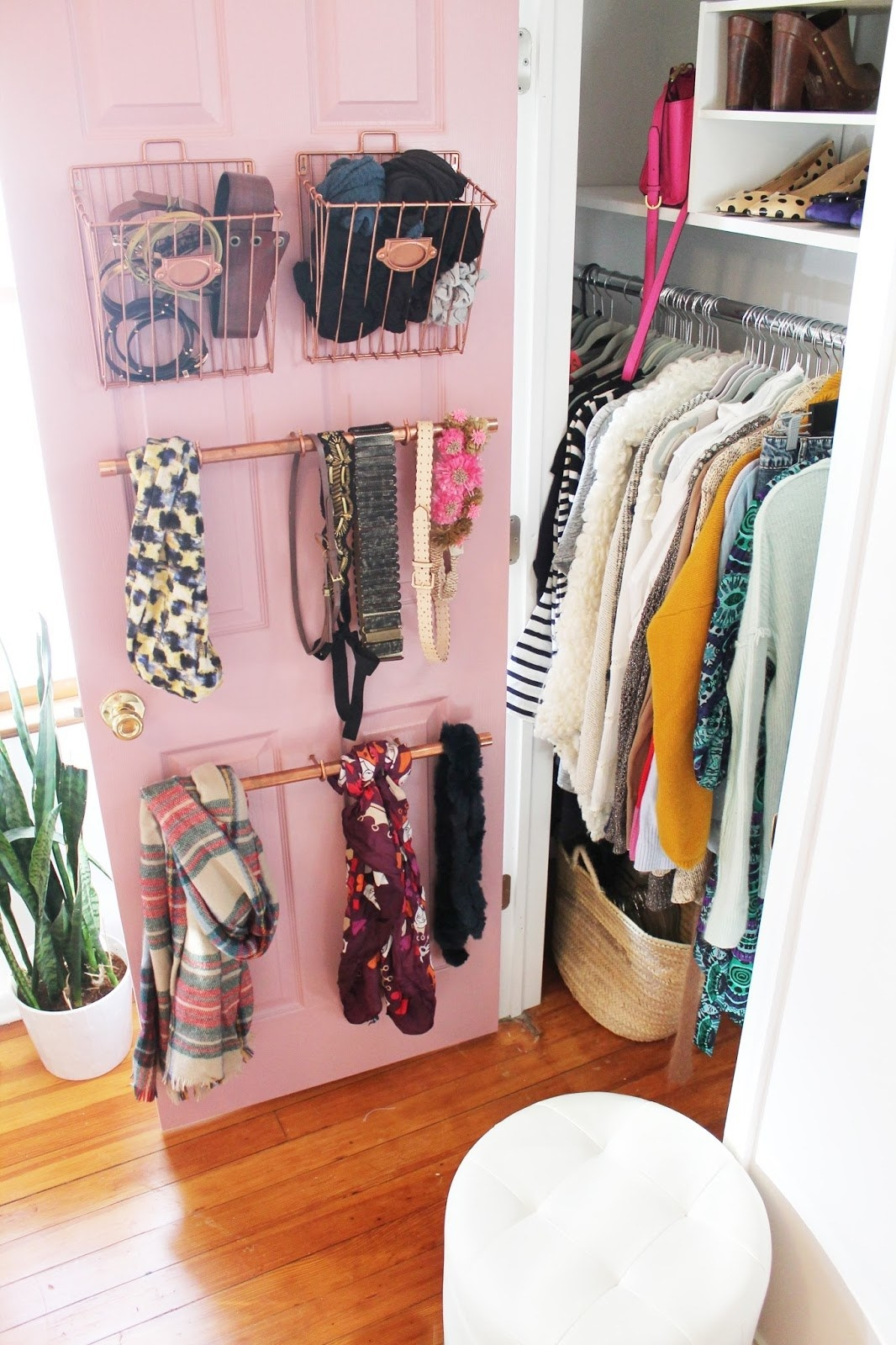 Cute pink closet door with two copper baskets holding belts and tights, and two copper bars holding scarves and other belts