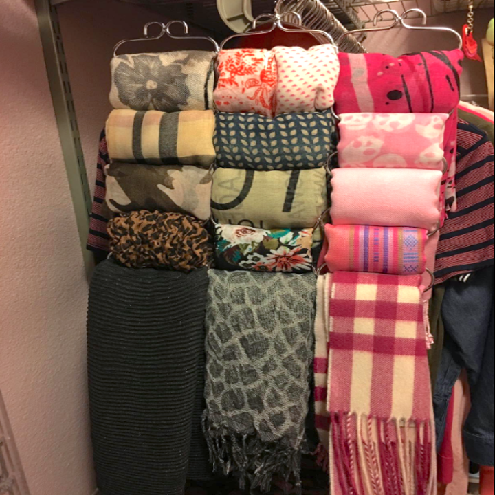 A customer review photo of all their scarves neatly folded and hung on the hanger