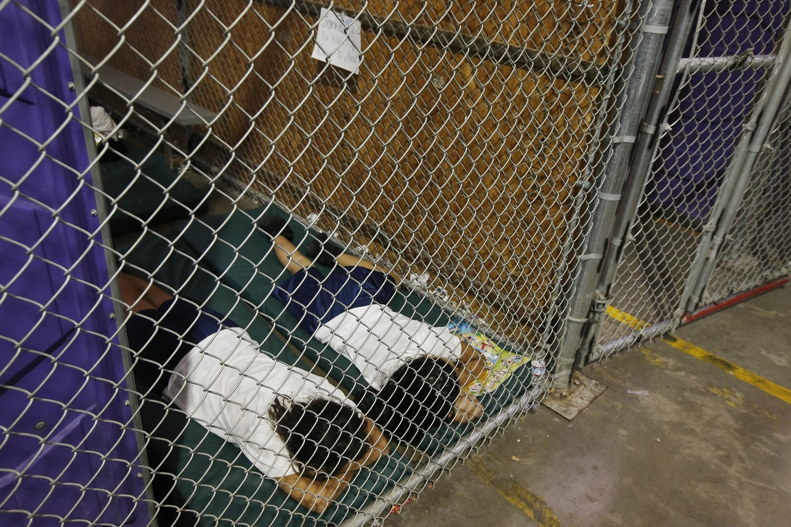 Two female detainees sleep in a holding cell at the US Customs and Border Protection Nogales Placement Center in Nogales, Arizona, in 2014.