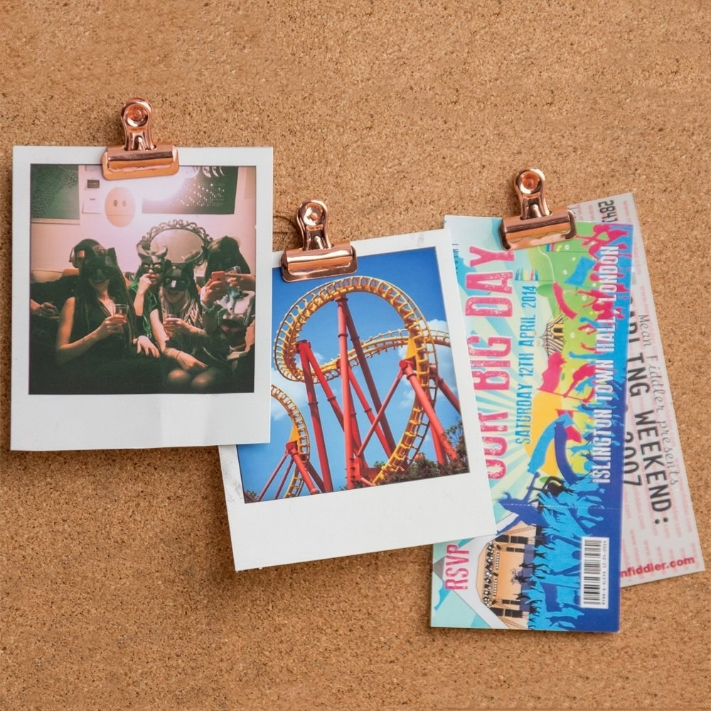 polaroids and concert tickets held up with clips on a corkboard
