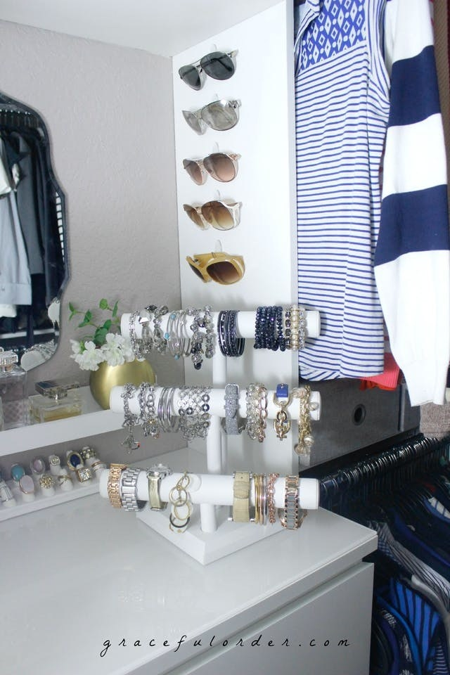 Blogger's five sunglasses hung on a side wall of a closet over a three-tier T-bar jewelry stand sitting on some drawers
