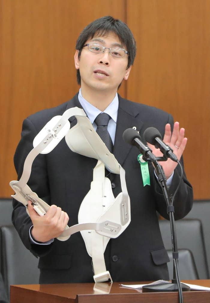 自身の身につけていたコルセットを外して、国会議員に受動喫煙の害を訴える長谷川一男さん